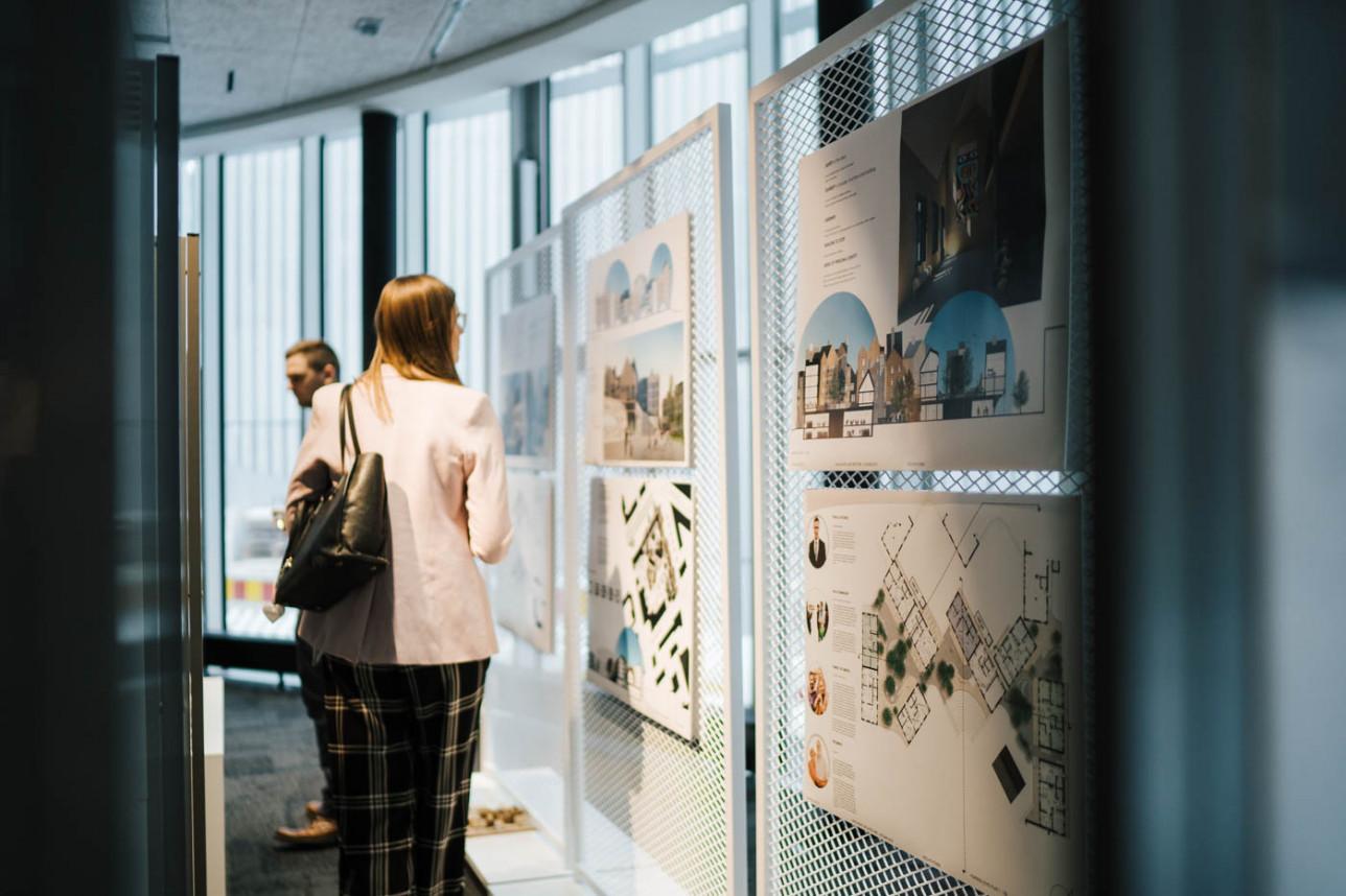 Ihmisiä katsomassa teoksia näyttelysermeissä.