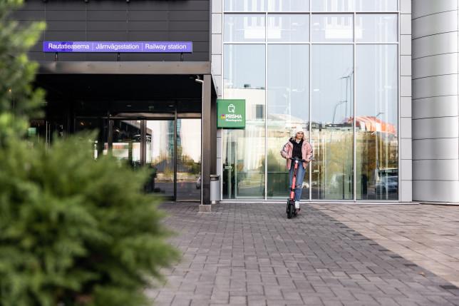 Tyttö sähköpotkulaudan kanssa Kupittaan rautatieaseman sisäänkäynnin luona.