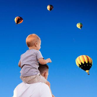 Mies ja pieni poika katsovat taivaalla lentäviä kuumailmapalloja